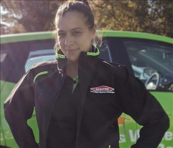 Servpro of Freehold shares picture of one of their female project managers and standing in front of their SERVPRO vehicle.