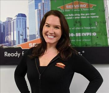 Servpro of Freehold shares picture of one of their project managers smiling and standing in front of a SERVPRO Ad picture.