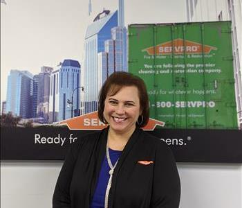 SERVPRO of Freehold shares picture of one of their females project managers smiling and standing in front of a SERVPRO Ad.