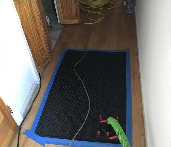 Black mats placed on a wood floor.