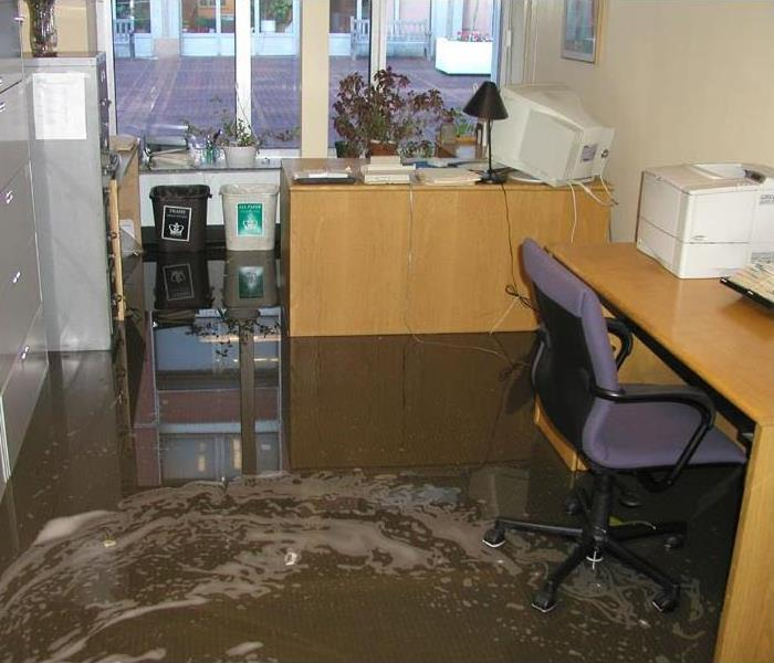 An office with water swirling on the floor.